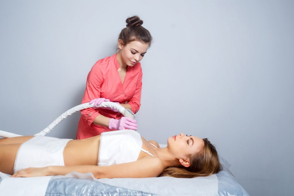 woman laying peacefully while aesthetician performs CoolSculpting procedure