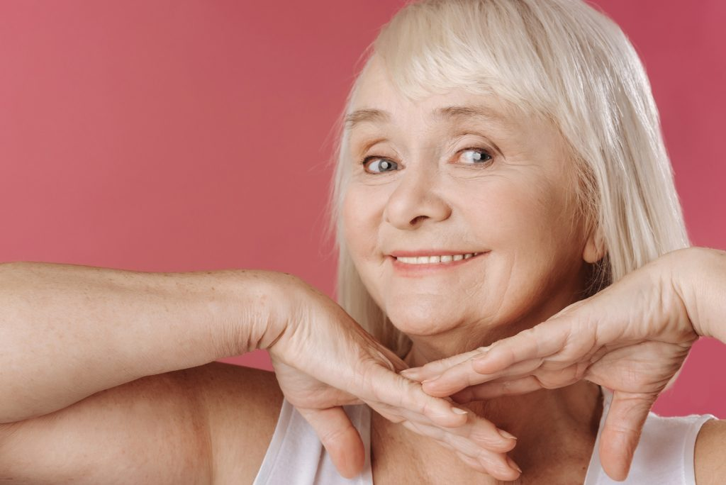 Older Woman Smiling With Hands Under Face